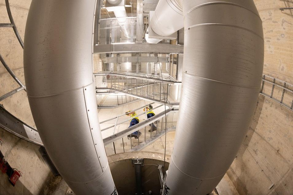 Ein Blick von unten hinauf zum Einstieg. Dicke Fernwärmerohre prägen das Bild. Über viele Treppen geht es 21 Meter hinab bis zum neuen Tunnel.