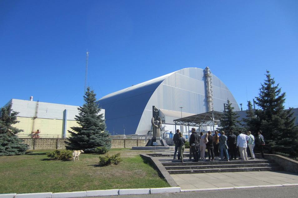 Eine Touristengruppe steht am Mahnmal vor dem 1986 explodierten Block vier des Atomkraftwerks Tschernobyl in der Ukraine.