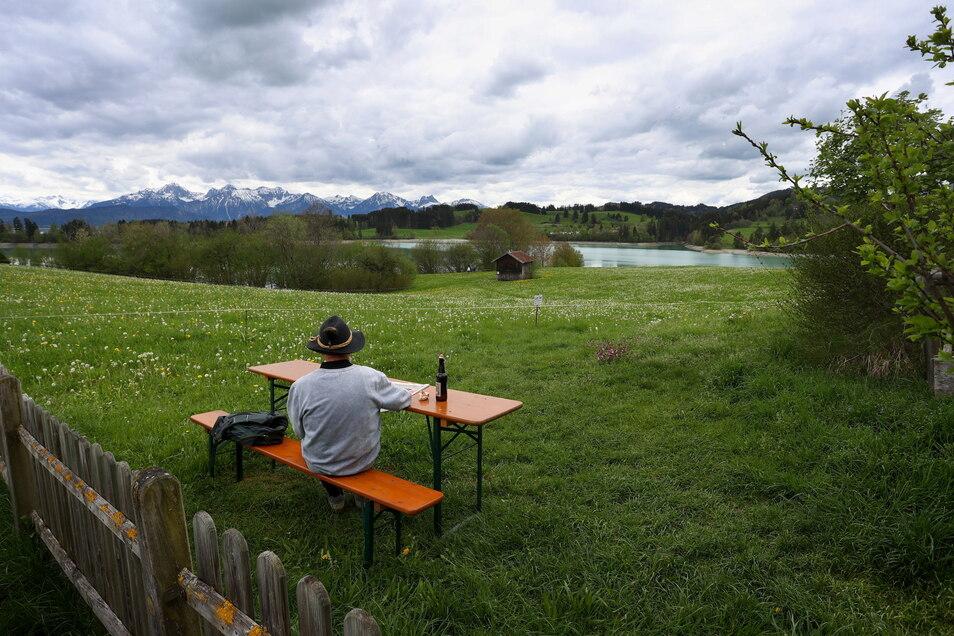 Ein Ausflügler sitzt am Forggensee. In bayerischen Regionen mit einer stabilen Sieben-Tage-Inzidenz unter 100 dürfen am Pfingstwochenende Hotels öffnen.