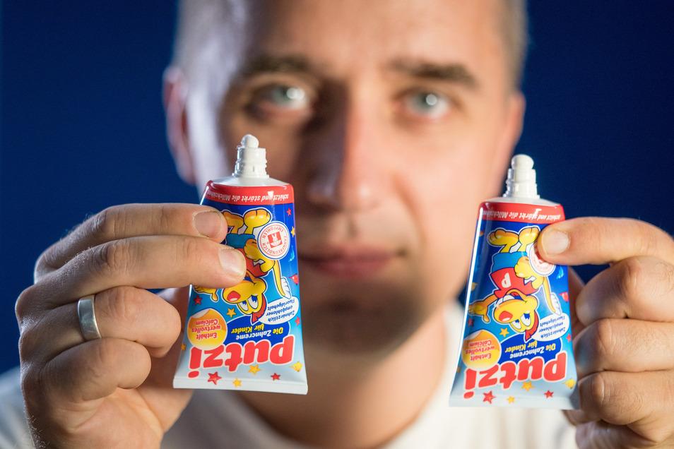 """Rund drei Millionen Tuben """"Putzi"""" produziert die Dresdner Firma Dental Kosmetik pro Jahr – nun mit höherer Fluoridkonzentration und veränderter Tubenöffnung. Qualitätschef Dr. Konrad Hohlfeld zeigt altes und neues (li.) Modell."""