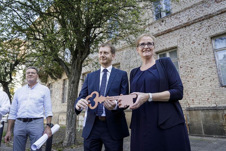 Ministerpräsident Michael Kretschmer überreicht Mittwoch einen symbolischen Schlüssel an Cornelia Maiwald-Immer, Vorsitzende des Evangelischen Schulvereins Niesky/Görlitz. Architekt Michael Noack hat die Sanierungspläne dabei.