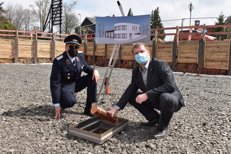 Bürgermeister Thomas Paul (rechts) und Gemeindewehrleiter Armin Groß versenken die Zeitkapsel im Fundament.