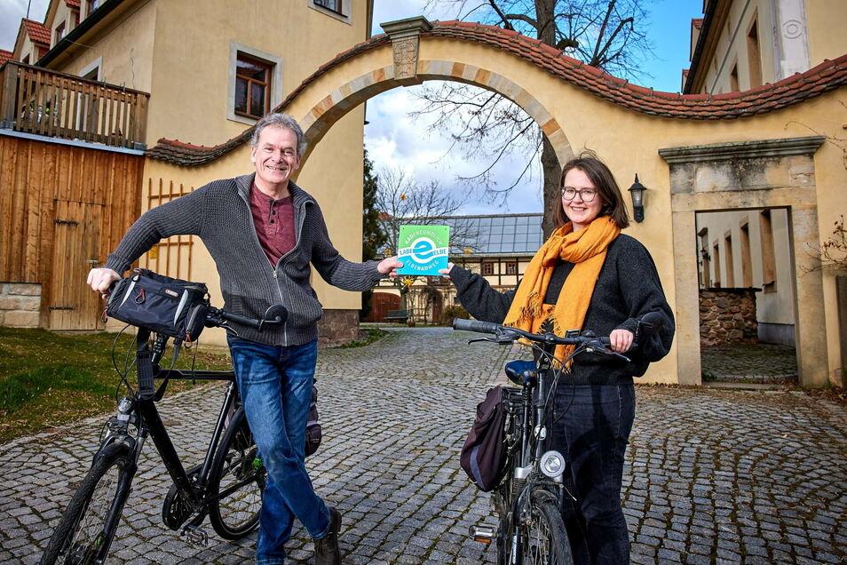 An dieser grün-blauen Plakette erkennen Radler die Unterkünfte: Elberadweg-Koordinatorin Heike Grunow übergibt sie an Hotelier Roland Taubinger vom Landhotel Gut Wildberg in Klipphausen.