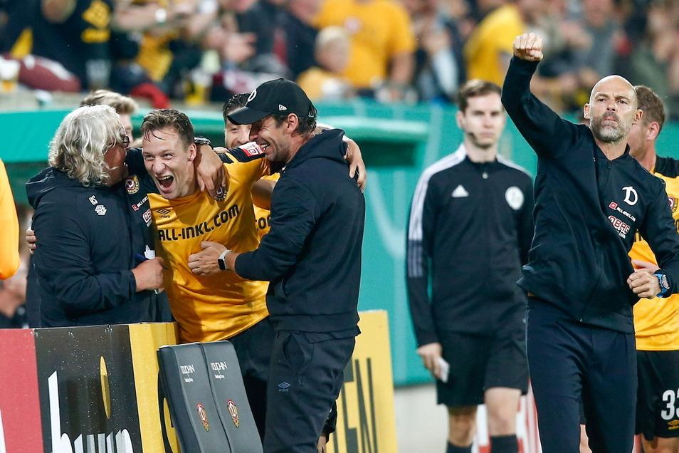 Nach seinem Tor schreit Tim Knipping seine Freude heraus und läuft zur Bank, umarmt die Co-Trainer Heiko Scholz (l.) und Ferydoon Zandi. Chefcoach Alexander Schmidt (r.) zeigt die Jubel-Faust.
