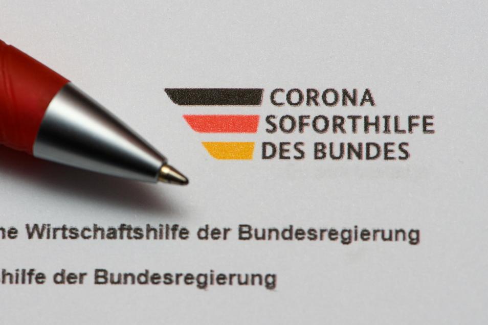 """Ein Stift liegt auf einem Antrag auf Gewährung der """"Novemberhilfe"""" als außerordentliche Wirtschaftshilfe der Bundesregierung in der Corona-Krise."""