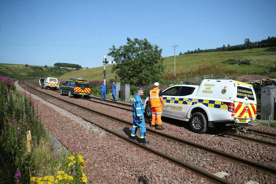 12.08.2020, Großbritannien, Stonehaven: Notfallfahrzeuge und Einsatzkräfte stehen auf Schienen. Bei einem Zugunglück in Schottland sind nach Medienberichten vermutlich drei Menschen ums Leben gekommen, darunter auch der Lokführer. Der Zug entgleiste a
