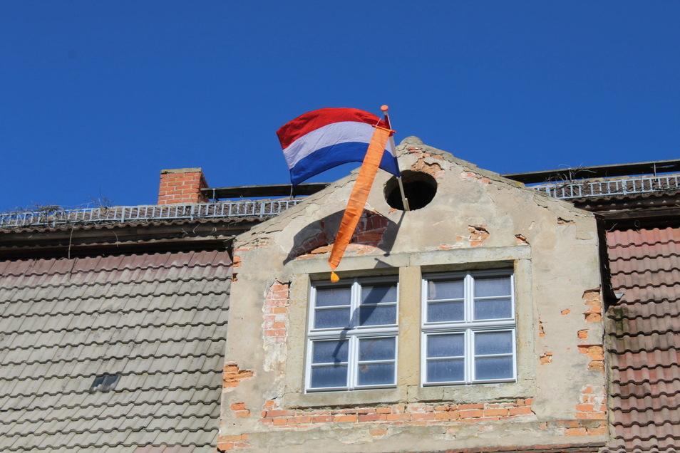 Aus einem Gaupenfenster an der Schlossfassade in Tiefenau weht die holländische Flagge.