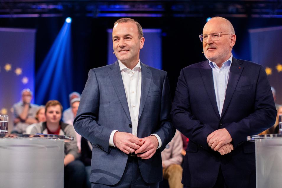 """Manfred Weber (l, EVP) und Frans Timmermans (SPE), Spitzenkandidaten für die Europawahl, stehen vor der Live-Sendung """"Wahlarena zur Europawahl"""" im Fernsehstudio nebeneinander."""