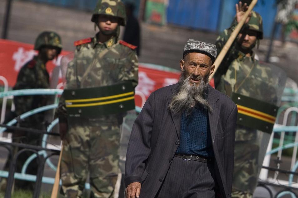 ARCHIV - 07.07.2009, China, Ürümqi: Ein Angehöriger der uigurischen Minderheit in China geht in der Unruheregion Xinjiang in Nordwestchina vorbei an chinesischen Sicherheitskräften.