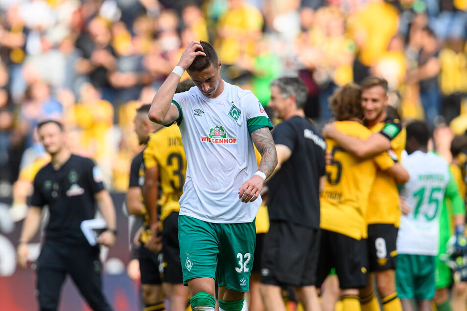 Während der Bremer Marco Friedl nach dem Schlusspfiff enttäuscht vom Rasen schleicht, feiern im Hintergrund die Dresdner.