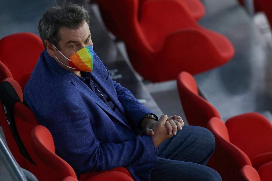 Bayerns Ministerpräsident Markus Söder sitzt mit einer Regenbogenmaske auf der Tribüne.