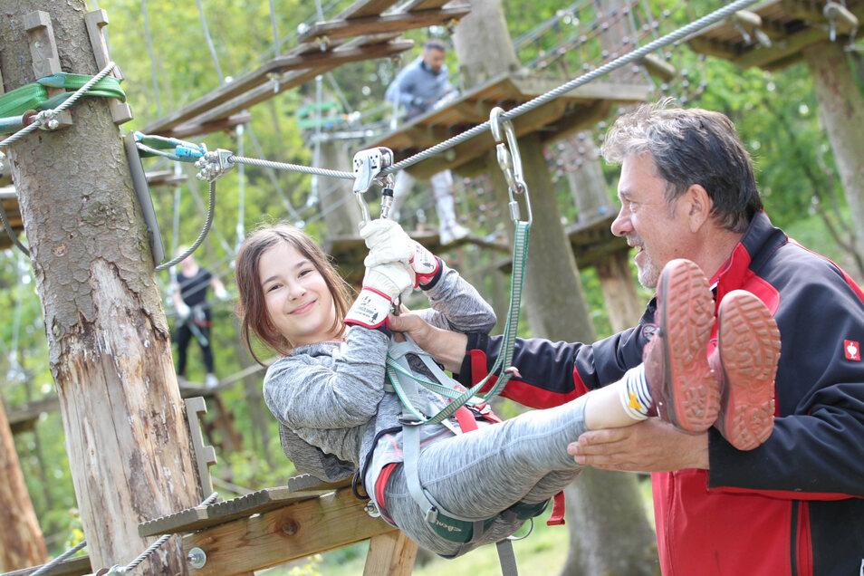Endlich wieder klettern: Lina Petermann (10) freut sich mit dem Betreiber des Kletterwaldes an der Talsperre Pöhl, Jörg Böhm, um die Wette.