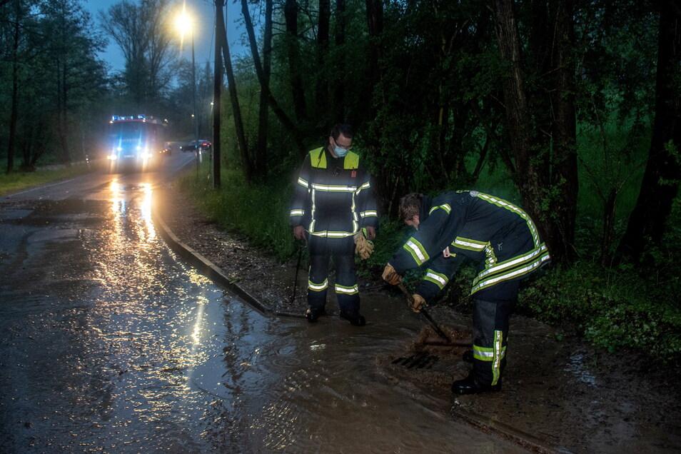 Feuerwehrleute versuchen in Steina das schlammige Wasser von der Straße abzuleiten.