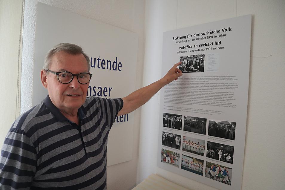 """Reinhardt Schneider ist seit 2002 Vorsitzender des Fördervereins Begegnungsstätte Zejler-Smoler-Haus Lohsa e. V.. Vor Ort in der Dauerausstellung zeigt er auf die Erinnerungstafel zum Thema """"30 Jahre Stiftung für das sorbische Volk""""."""