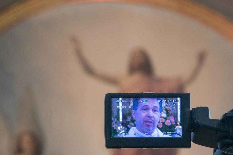 Pfarrer Daniel Dzikiewicz ist auf dem Bildschirm einer Videokamera während der Übertragung des Ostergottesdienstes aus der katholischen Kirche in Crostwitz zu sehen.