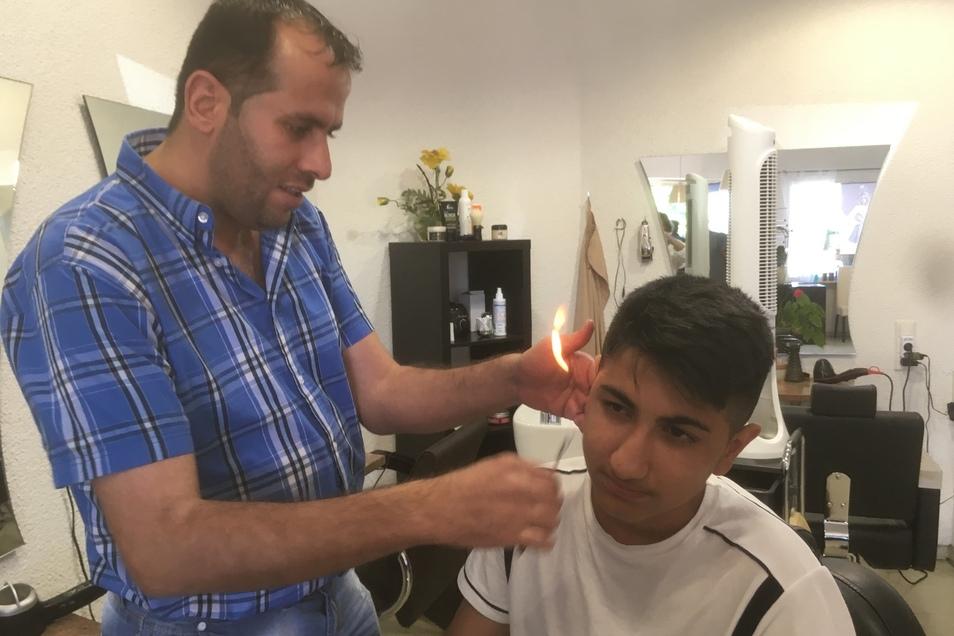 Mit einem Stück brennender Watte flämmt Friseur Waseem Ohr-Haare ab.