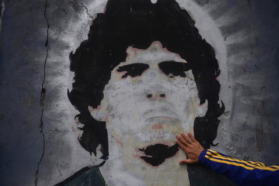 Argentinien, Buenos Aires: Ein Fan trauert vor einem Wandgemälde mit der Abbildung des ehemaligen Fußballstars Maradona.
