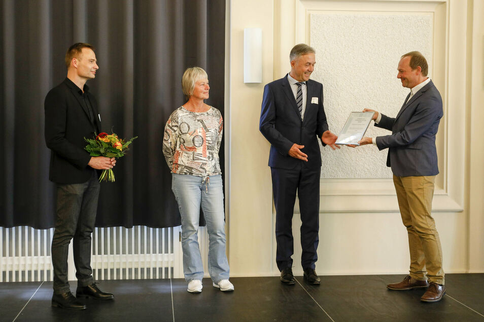 Ein Preis für Gröditz: Umweltminister Wolfram Günther (Grüne) überreicht eine Urkunde an Bürgermeister Jochen Reinicke, der von Simone Helbig von der Stadtverwaltung begleitet wird. Tilman Werner von der Saena hält die Blumen (v.r.).