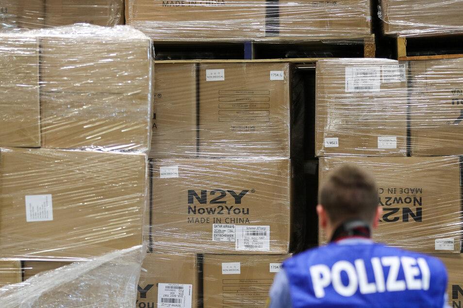 Ein Polizist steht vor Kartons mit Schutzmasken aus China.