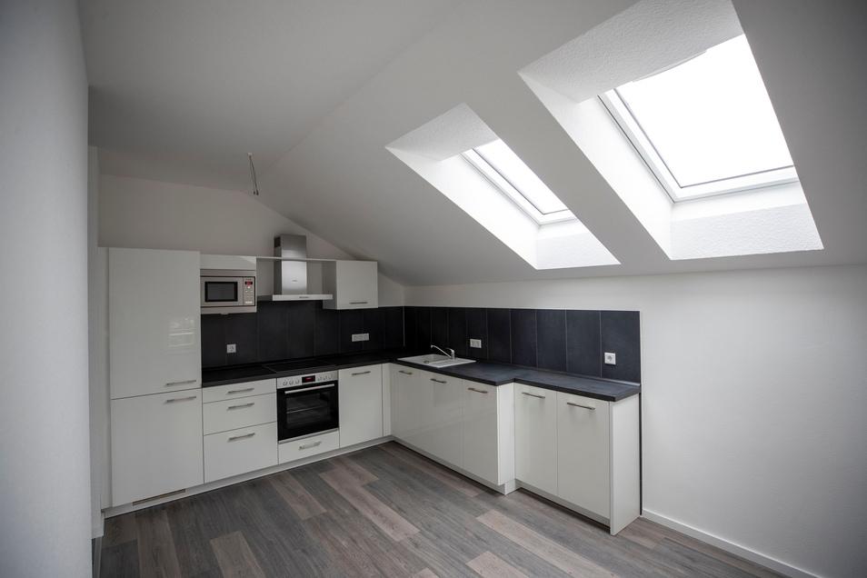 Blick in die Küche: Weiße Einbauküchen sind in allen Wohnungen Standard. Die Dachfenster haben elektrische Außenjalousien.