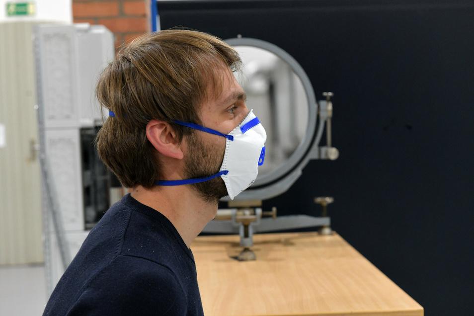 Mitarbeiter Emanuel Thom spricht durch eine Maske. Der Schlierenspiegel im Hintergrund bündelt LED-Lichtstrahlen, reflektiert sie und macht so die Aerosole sichtbar.