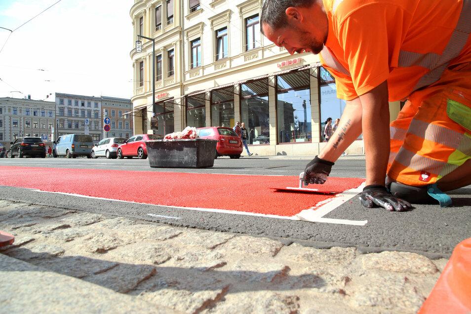 Alex Rutta spachtelt die rote Farbe auf den Asphalt. Die Firma Verkehrstechnik Seifert markiert am Postplatz in Görlitz die Fahrbahn.