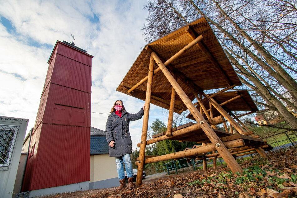 Jessica Prosch-Keller steht an der neuen Sitzgelegenheit, die am Gerätehaus aufgestellt wurde. Diese soll auch von Wanderern genutzt werden.