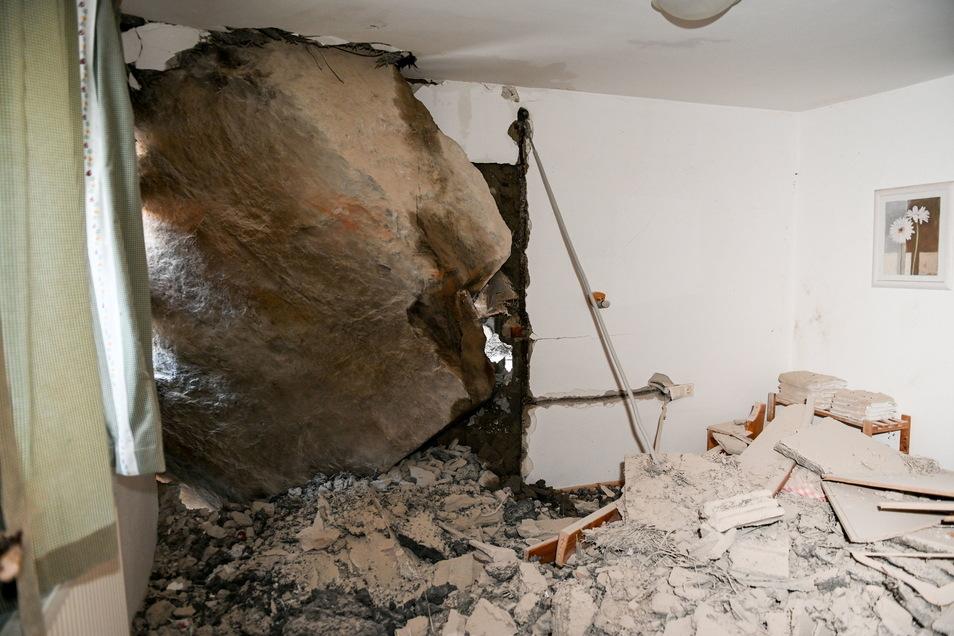 Ein mehrere Meter hoher Felsblock steckt in einer Hauswand.