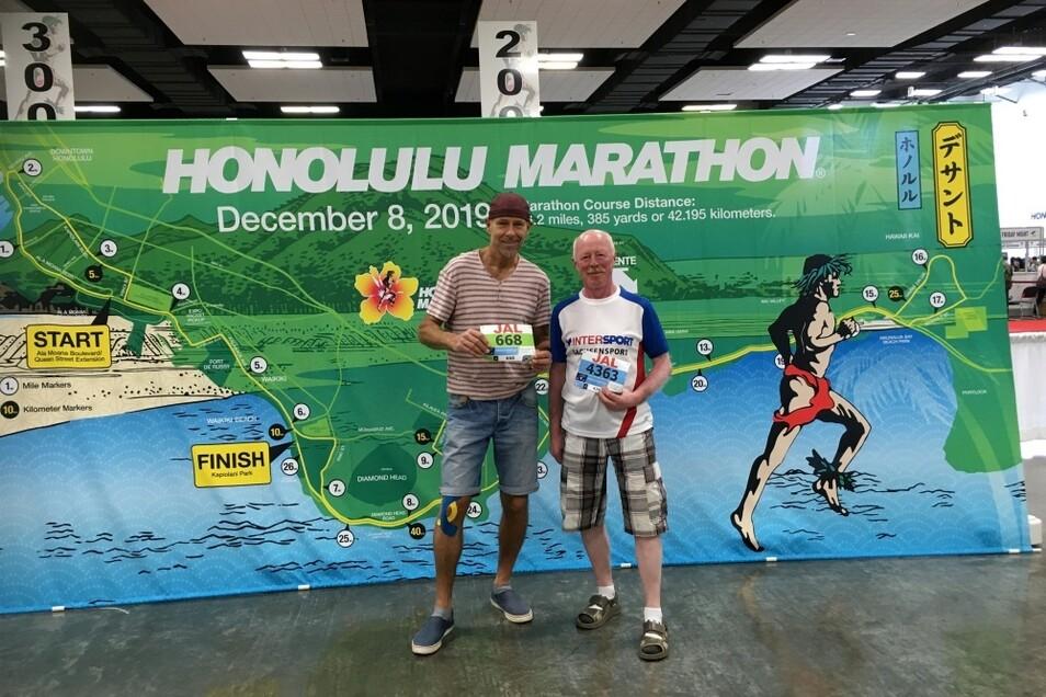 Uli Hayne (links) und Bodo Raschke (rechts) in Honolulu mit ihren originalen Startnummern vor einem Plakat mit der offiziellen Streckenführung.