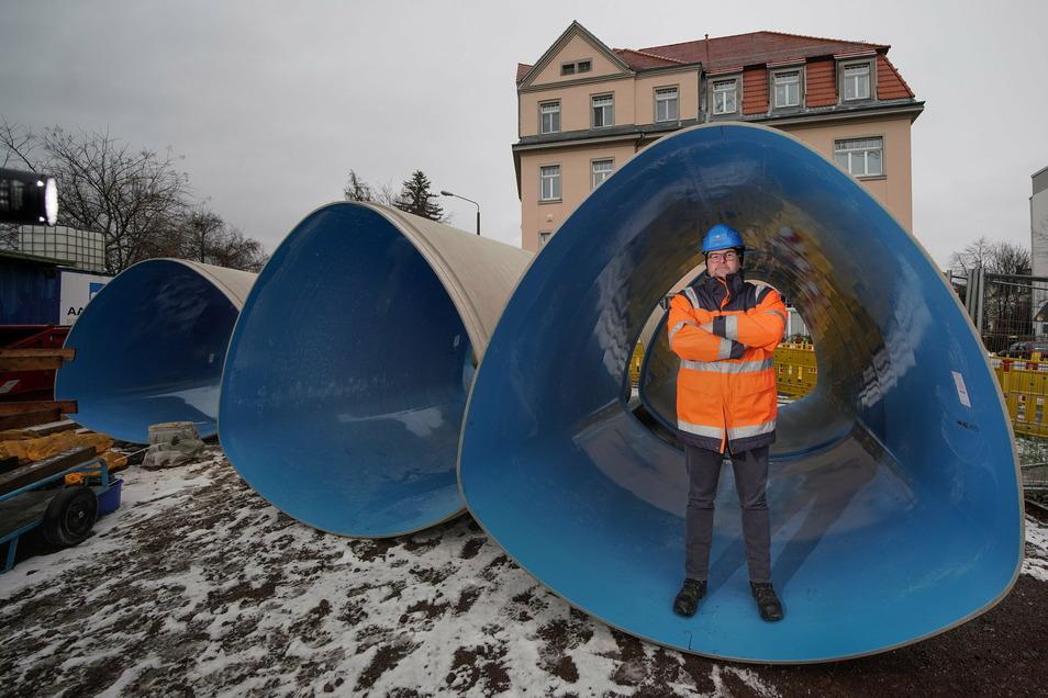 Bauleiter Mirko Knechtel in einem der glasfaserverstärkten Kunststoffrohre. Am Kranarm schweben sie später in die Baugrube zum Kanal.