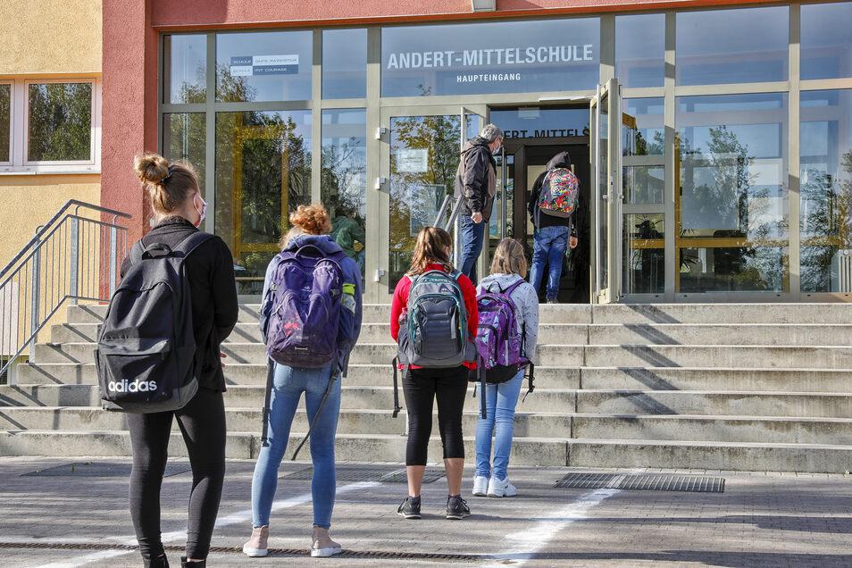 Schlange stehen am Morgen: Nur einzeln dürfen die Kinder ins Schulhaus. Wartebereiche mit genügend Abstand sind mit Kreide auf das Schulhof-Pflaster aufgezeichnet.