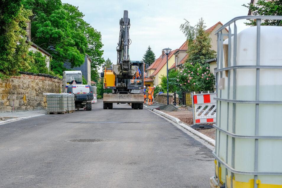 Zwischen Gerhart-Hauptmann-Straße und Hausbergweg ist der Asphalt schon auf der Fahrbahn. Die Bauarbeiter pflastern jetzt den neuen Gehweg.