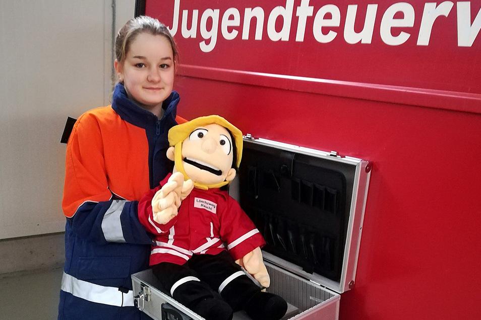 Vivien von der Jugendfeuerwehr Leisnig zeigt die Handpuppe aus einem der neuen Ausbildungskoffer.