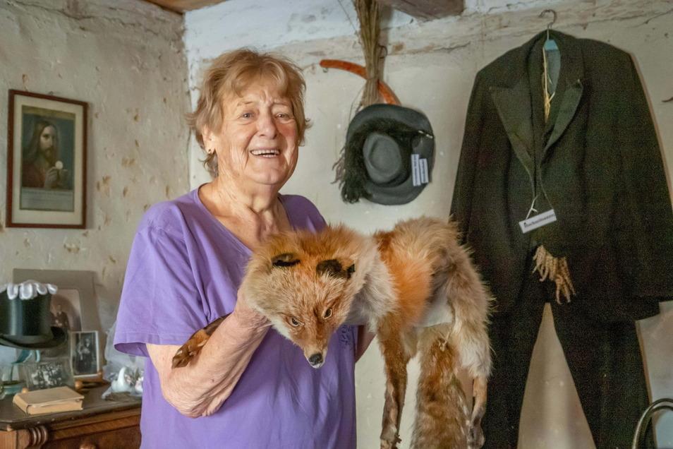 Die Fuchsstola, die Regina Bonk in den Händen hält, hat sie fürs Heimatmuseum geschenkt bekommen. Die Räume des Küsterhauses sind wie eine Wohnung eingerichtet. Hier steht sie gerade im Schlafzimmer, an der Wand hängt ein Anzug.