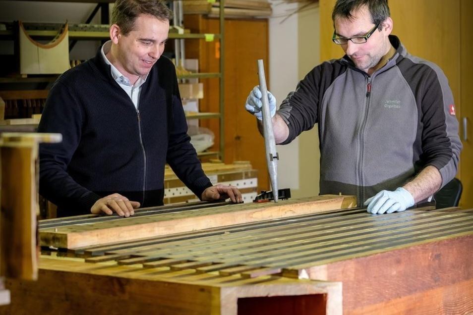 Geschäftsführer Ralf Jehmlich (l.) und Mitarbeiter Michael Kronesser an einer Windlade der Radeburger Orgel