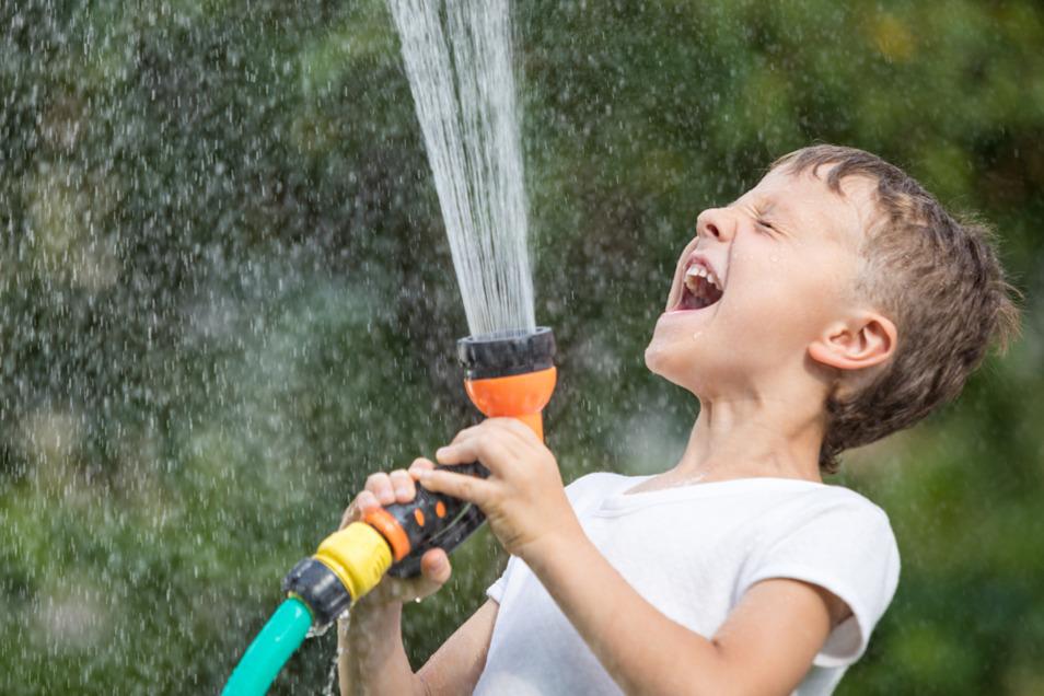 Ran an den Gartenschlauch: Es muss nicht immer ein großer Pool sein. Auch einfache Alltagsgegenstände wie Rasensprenger oder Sprühflaschen sorgen für Abkühlung und jede Menge Spaß.