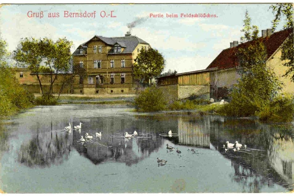 """Diese Ansichtskarte zeigt die Gaststätte """"Zum Feldschlößchen"""". Das Gebäude an sich steht noch, der Teich wurde längst zugeschüttet. Heute finden auf dem Areal im Alten Bauerndorf ab und an kleine Feste statt."""