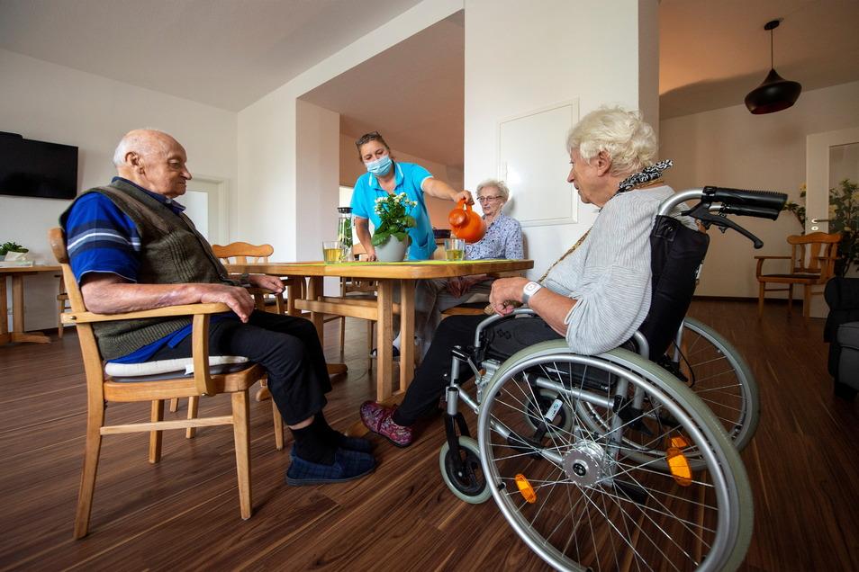 Katharina und Gerhard Schwarz (l.) sowie Annemarie Schelle (r.) trinken gemeinsam mit Pflegekraft Eva im Treff der Tagespflege im ehemaligen Gasthof Grauer Storch eine Tasse Tee.