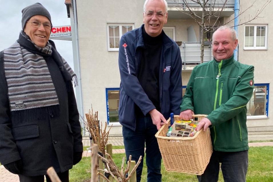 Ortsvorsteher Karlheinz Deutsch (l.) und Eyk Flasche (r.) übergaben Thomas Hesse vom DRK-Pflegeheim die Obststräucher und einen Kob mit Blumenzwiebeln.