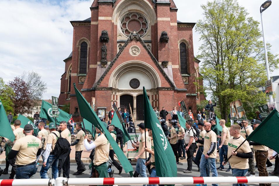 """Teilnehmer eines rechten Aufmarsches der Partei """"Der dritte Weg"""" gehen vor der Pauluskirche in Plauen entlang."""