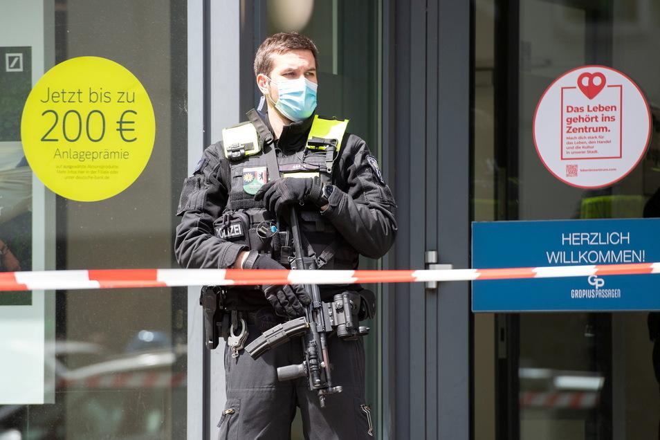 Ein Polizeibeamter steht mit einer Maschinenpistole vor einer Bankfiliale in den Gropius Passagen in Neukölln. Bei einem Raubüberfall auf einen Geldboten wurde ein Täter angeschossen.