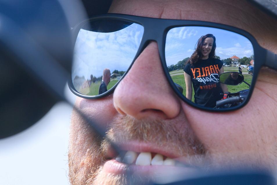 """Daniela Hesse, Leiterin der """"Harley Days Dresden 2021"""" spiegelt sich in der Sonnenbrille eines Mitglieds im Dresdner Harley Davidson Club, """"Dresden Chapter Germany Harley Owners Group""""."""