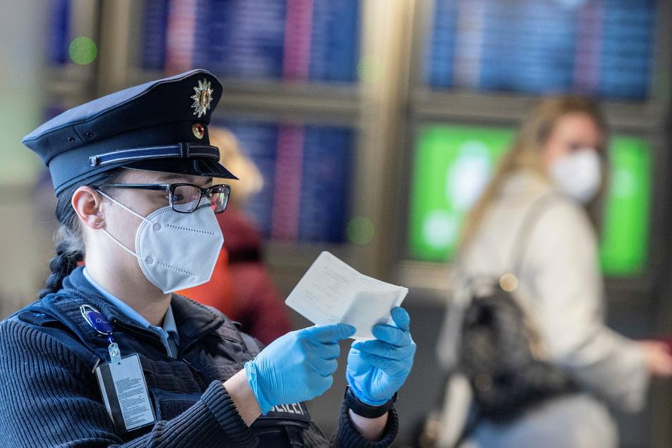Eine Beamtin der Bundespolizei kontrolliert am Flughafen Frankfurt ein Dokument eines Passagiers. Wer als Passagier aus einem der von Corona besonders betroffenen Staaten nach Deutschland einreist, muss einen negativen, aktuellen Corona-Test vorweisen kön