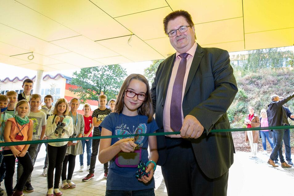 Bürgermeister Christoph Fröse und Viertklässlerin Isabell zerschneiden das blaue Band und eröffnen die neue Dreifeld-Sporthalle.