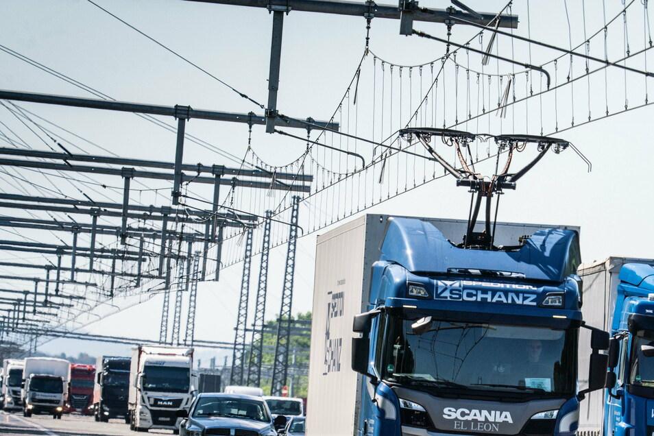 Ein Lkw fährt mit ausgefahrenem Stromabnehmer auf der ersten deutschen Teststrecke für E-Lastwagen mit Oberleitung auf der Autobahn 5.