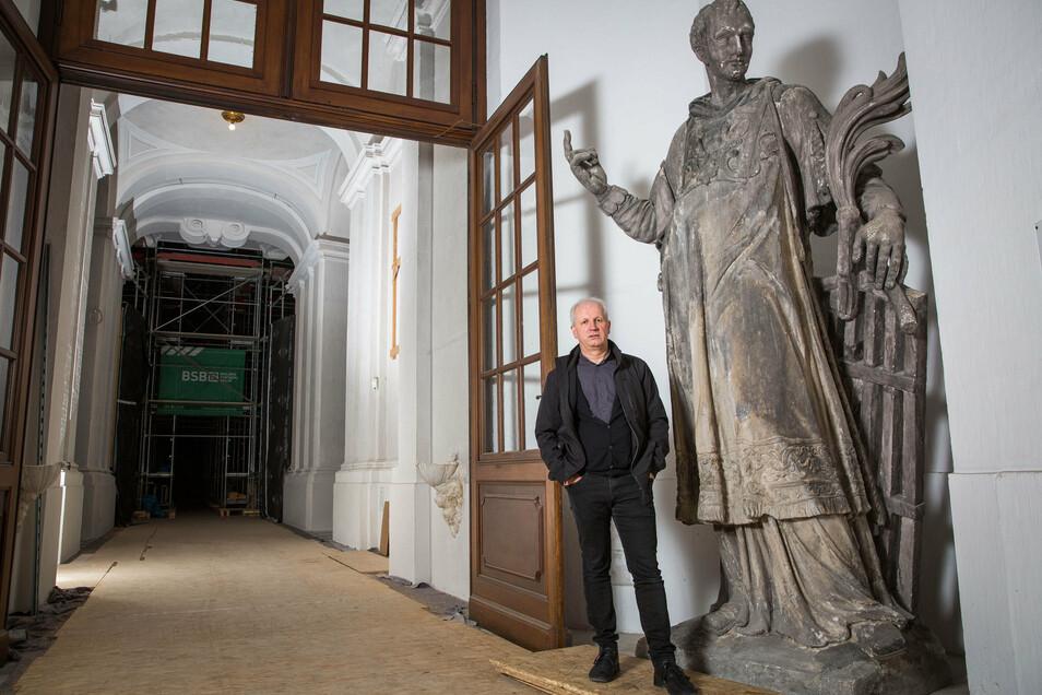 Dompfarrer Norbert Büchner im Eingangsbereich der Kathedrale neben der beschädigten Figur des heiligen Laurentius. Eine Kopie steht jetzt auf der Hofkirche.