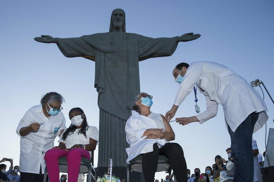 Zwei Frauen erhalten bei einem Impftermin vor der Christus-Statue eine Covid-19-Impfung.