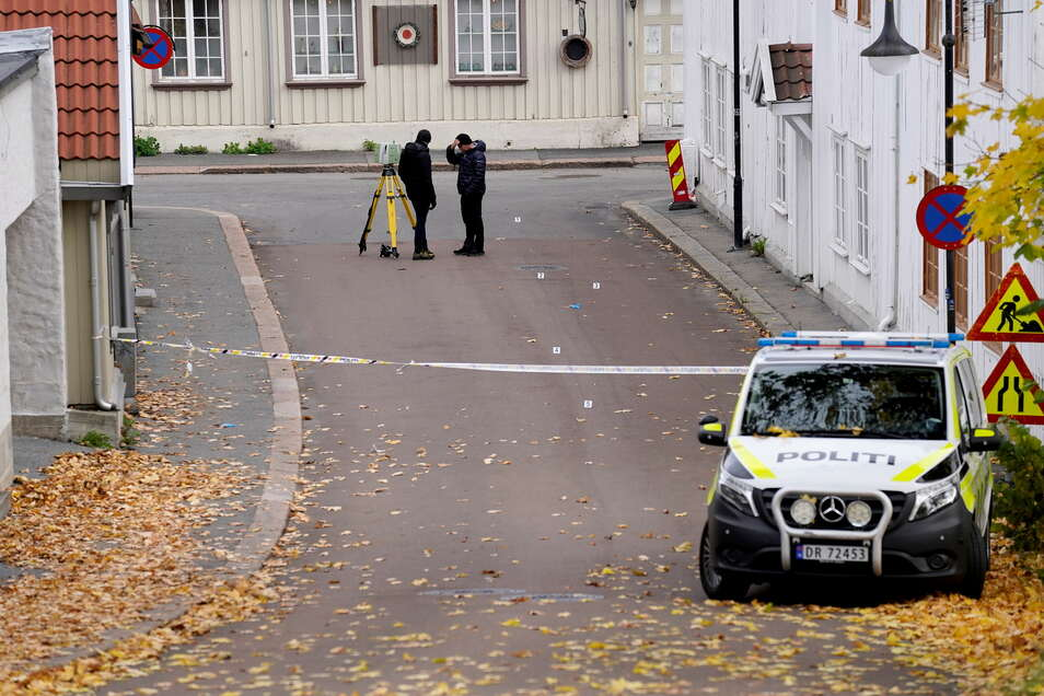Zwei Polizisten ermitteln in der Nähe des Tatorts nach einer Gewalttat in der norwegischen Kleinstadt Kongsberg.