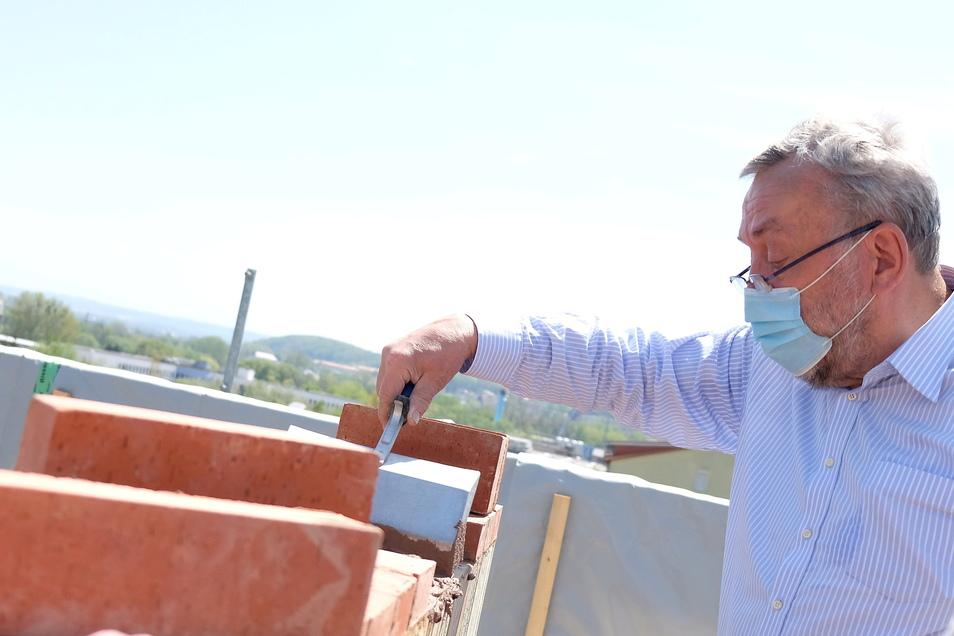 Setzt einen der Schlusssteine auf dem zweistöckigen Meißner Lehmhaus: Professor Wolfram Jäger aus Radebeul probiert in Meißen ein Modellprojekt für nachhaltiges Bauen aus.