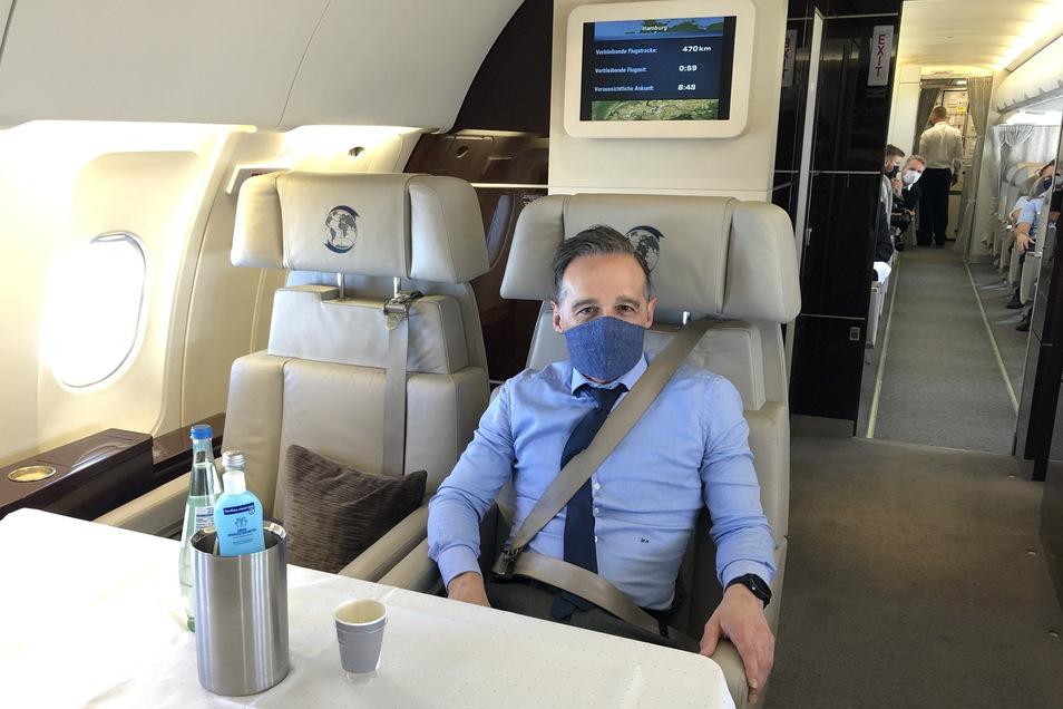 Heiko Maas (SPD), Außenminister, sitzt mit Mund- und Nasenschutz in einem Flugzeug der Luftwaffe.